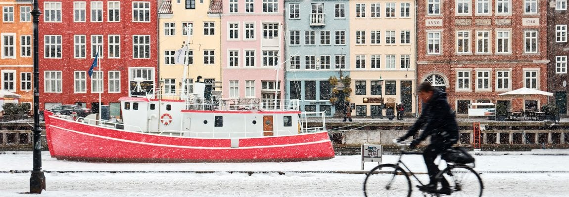 man riding bicycle in snowy copenhagen in winter