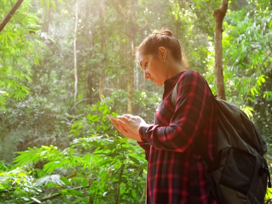 Lady wearing backpack and button down shirt in the rainforest