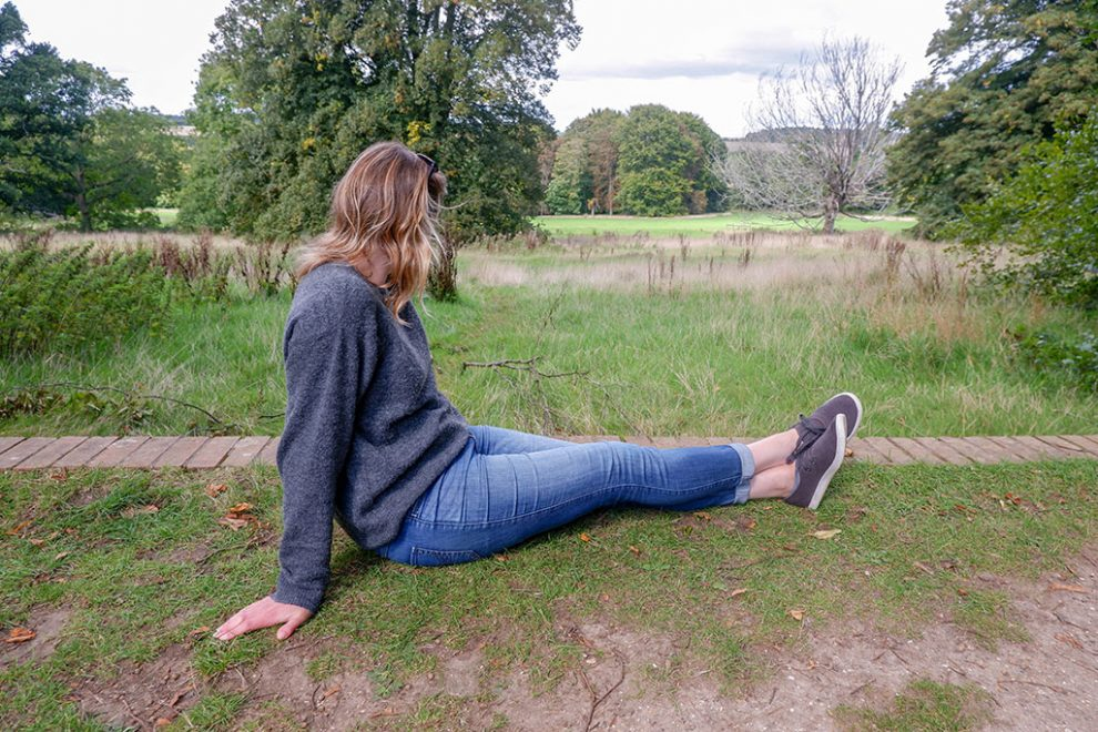 Lady wearing Allbirds Skippers while sitting on grass